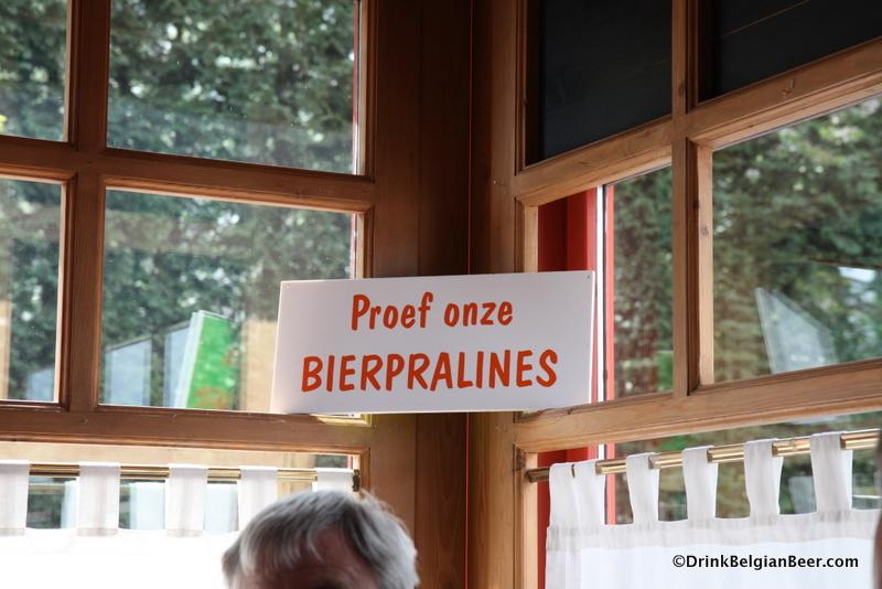 """The sign inside De Heeren van Liedekercke says """"Taste our Beer pralines."""""""