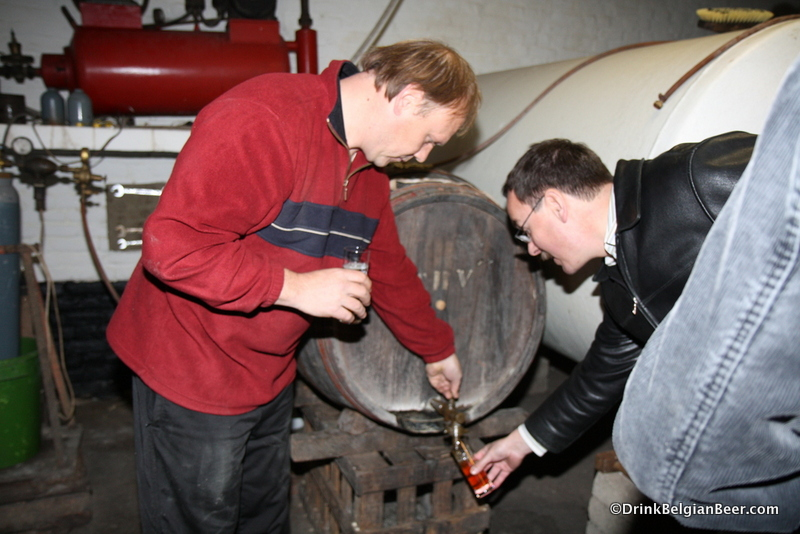 Hanssens blender John Matthys pulling a sample of kriekenlambiek from a barrel.