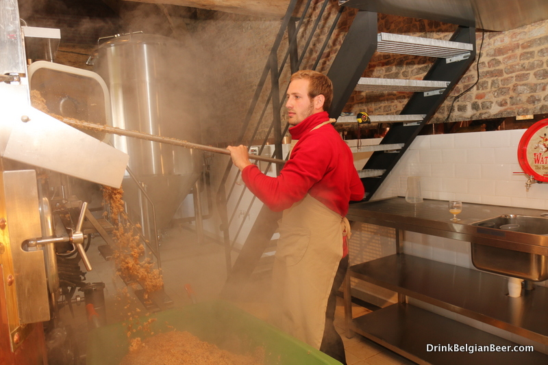 Anthony Martin's son, removing spent grains from the mash tun at Brasserie Waterloo.