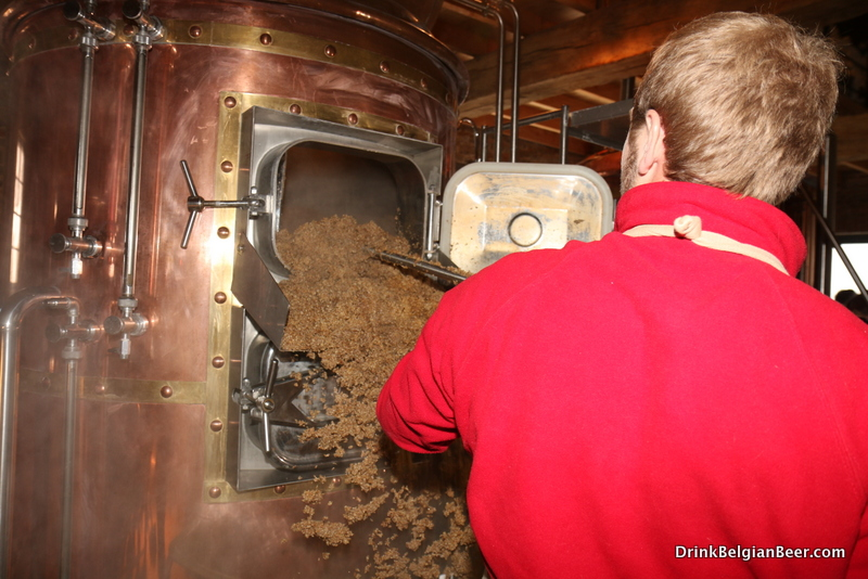 Edward Martin removing spent grains from the mash tun at Brasserie de Waterloo.