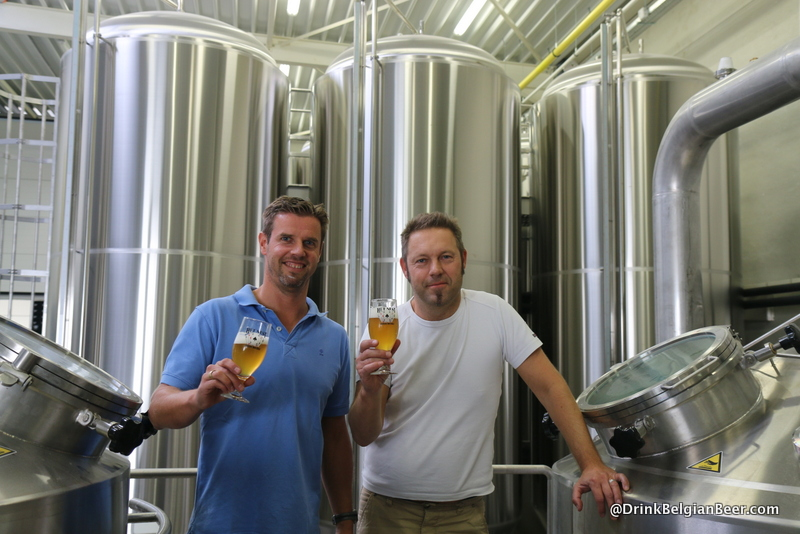 Filip and Guy in the brewhouse, with some fermenters behind them.