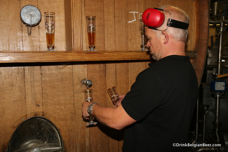 Lindemans brewmaster Peters Renders pulling samples of four year old lambic from a foeder.