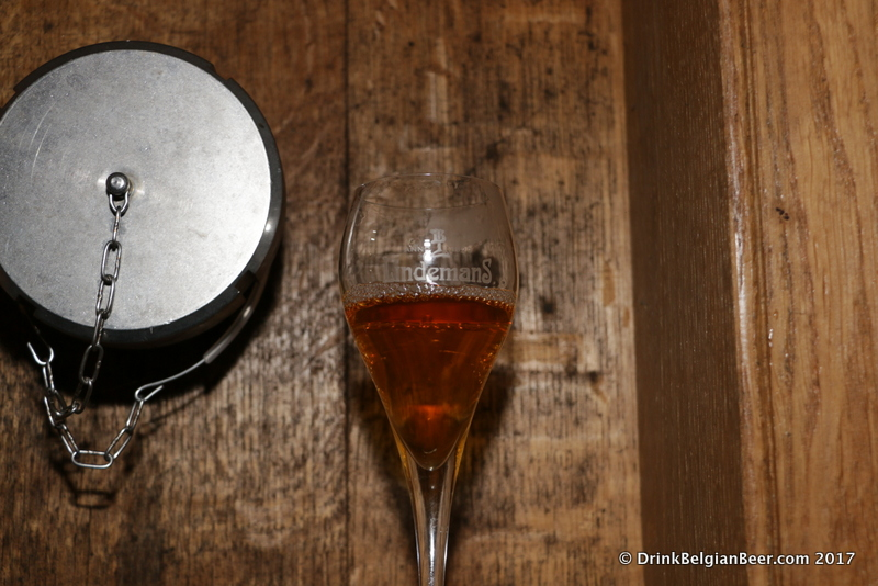 A glass of Lindemans lambic on a foeder.