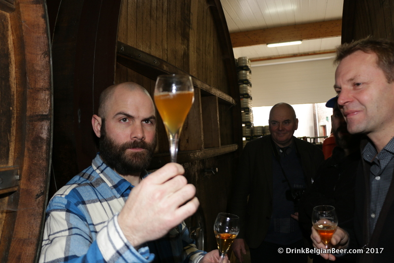 Dominic DeSantis (left) examining a glass of lambic as brewery owner Dirk Lindemans looks on.