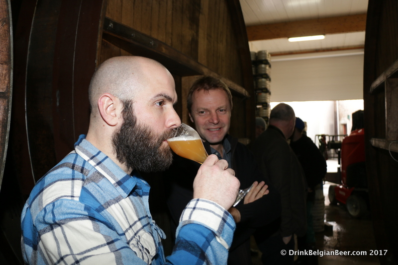Dominic DeSantis of Baltimore tastes a glass of lambic as brewery owner Dirk Lindemans looks on.