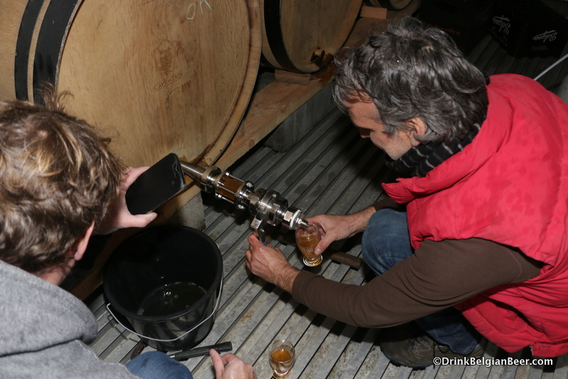 Jo Van Aert pulling samples of lambic from a barrel at Belgoo, as Jo Panneels looks on.