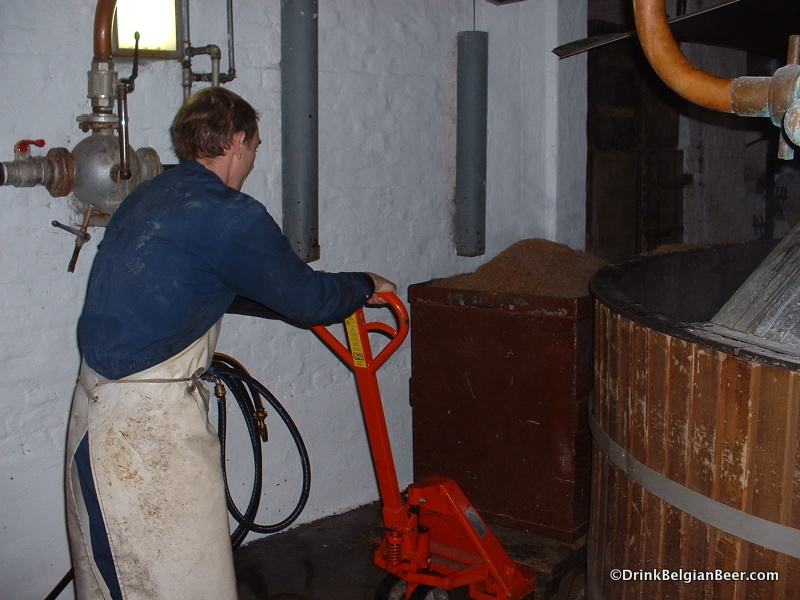 One of the Cantillon team prepares to roll a container full of spent grains out of the mash tun room in this 2003 photo.