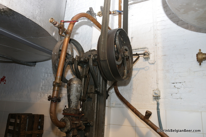A close up of an old pump with belt driven pulleys and piping.