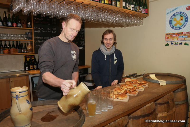 Jean Van Roy pouring the warm wort into glasses so those present can have a taste.