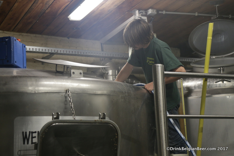 Diego Sachem cleans out the rest of the grains in the mash tun with a water hose.