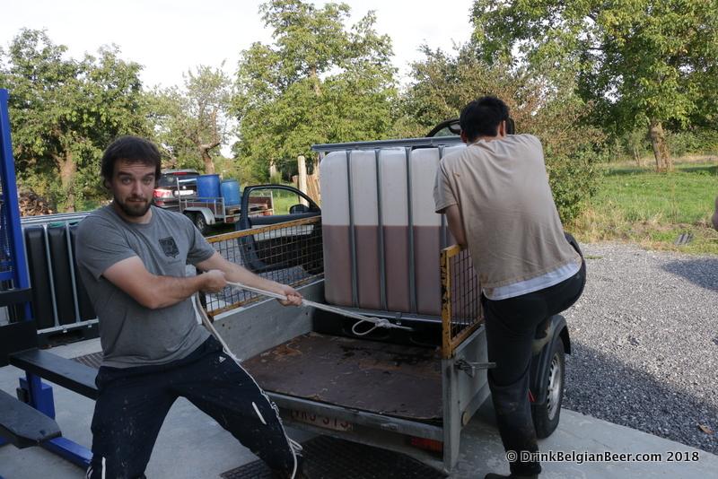 Raf Soef preparing to pull a container of fruit slush off a trailer at Stokerij Vanderlinden.
