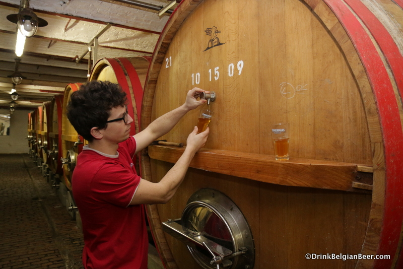 Brouwerij Timmermans brewer Kloris Deville pulling a glass of lambic from a foeder.