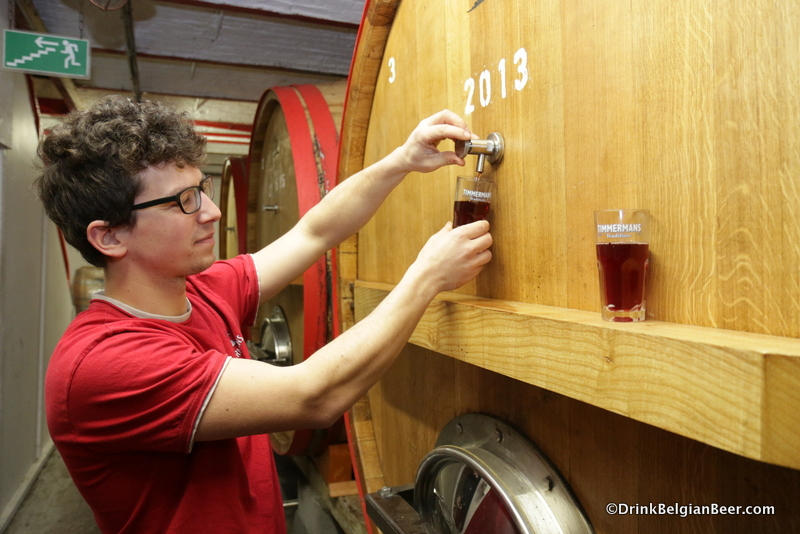 Brouwerij Timmermans brewer Kloris Deville pulling samples of kriekenlambiek from a foeder.