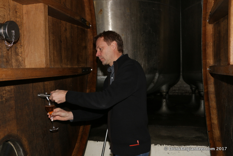 Dirk Lindemans pulls a glass of lambic right from a 100 hectoliter (85 U.S. barrel) foeder.